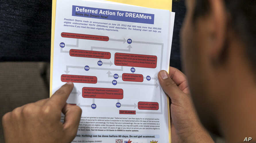 FILE - A legal immigrant reads a guide of the conditions needed to apply for the so-called 'DREAMers' Obama program, formally known as Deferred Action for Childhood Arrivals (DACA) at the Coalition for Humane Immigrant Rights, CHIRLA offices in Los A