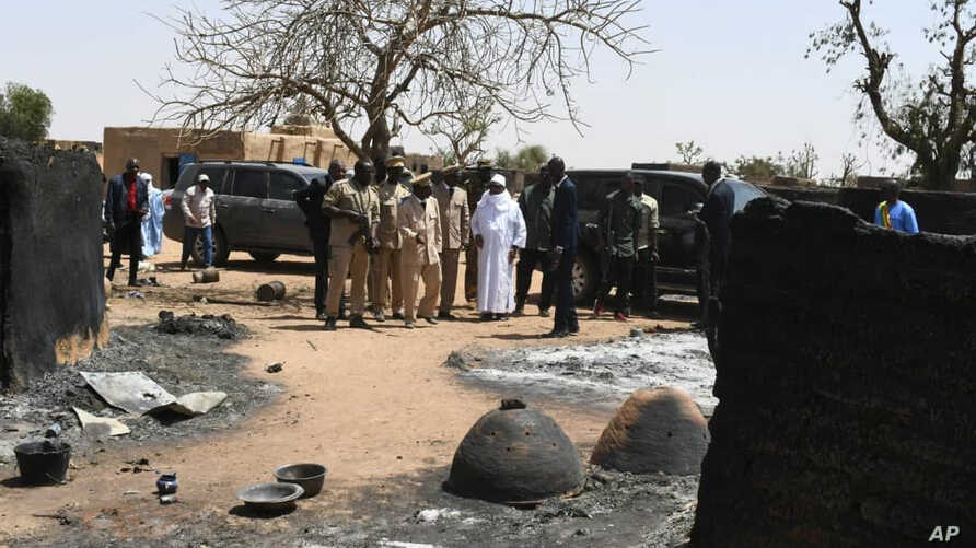 Mali's President Ibrahim Boubacar Keita inspects the damage after an attack by gunmen on Fulani herders in Ogossagou, Mali, March 25, 2019.