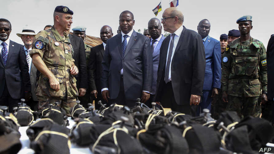 FILE - rench Defence Minister Jean-Yves Le Drian (C) flanked by President of the Central African Republic Faustin-Archange Touadera (2ndL), looks at military supplies at the Mpoko military base in Bangui, Oct. 31, 2016.