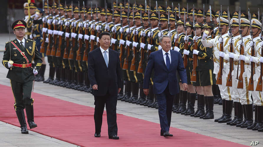 In this Aug. 31, 2015 file photo, Chinese President Xi Jinping, center, accompanies Kazakhstan President Nursultan Nazarbayev, right,  to view an honor guard during a welcoming ceremony outside the Great Hall of the People, in Beijing.