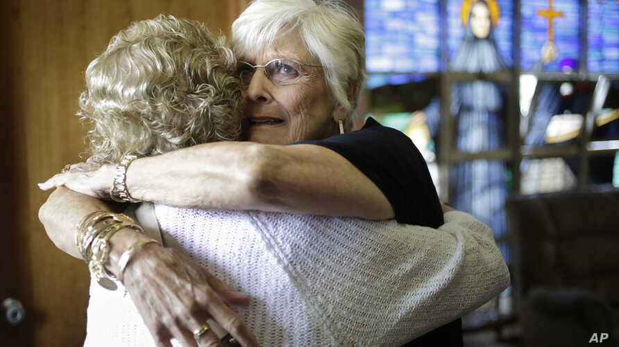 Nancy Shilts, of Scitutate, Massachusetts (R) hugs a fellow parishioner before a planned final service at St. Frances X. Cabrini Church, May 29, 2016, in Scituate.