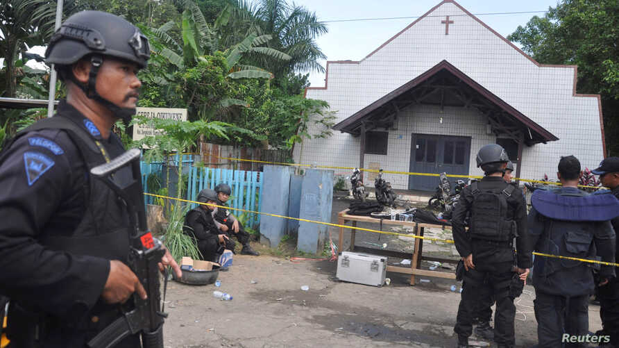 Police stand near the scene of an explosion outside a church in Samarinda, East Kalimantan, Indonesia, Nov. 13, 2016.