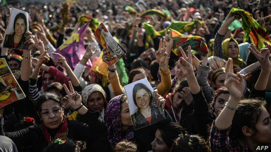 Kurds celebrating success by Kurd and peshmerga fighters to drive Islamic State militants out of Kobani, hold a photo of a fighter killed in the conflict, near the Turkish-Syrian border at Suruc, in Sanliurfa province, Jan. 27, 2015.