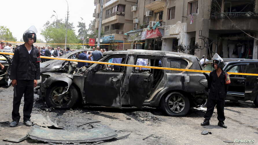 Policemen secure the site of a car bomb attack on the convoy of Egyptian public prosecutor Hisham Barakat near his house at Heliopolis district in Cairo, Egypt, June 29, 2015.