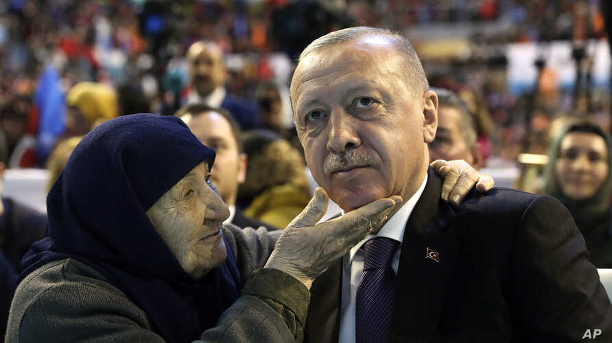 Turkey's President Recep Tayyip Erdogan with a supporter of his ruling Justice and Development Party, AKP, during a meeting with women in Sanliurfa, Turkey, March 8, 2019, ahead of local elections scheduled for March 31, 2019.