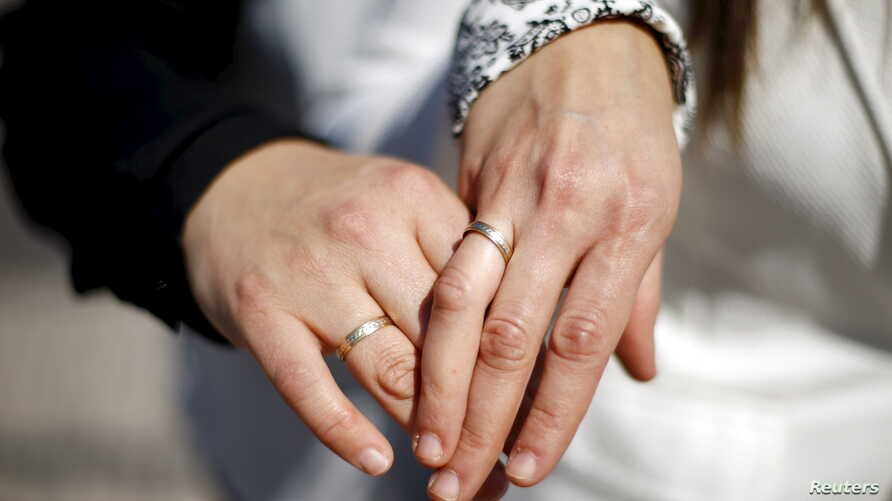 A same-sex couple displays rings in honor of their civil union, legal for the first time in Santiago, Chile, Oct. 22, 2015.