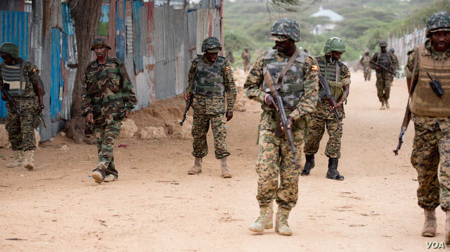 AMISOM soldiers and armored vehicles pass a woman riding a cart during a patrol at a village outside Mogadishu, Sept. 19, 2016. (Photo: J. Patinkin/VOA)