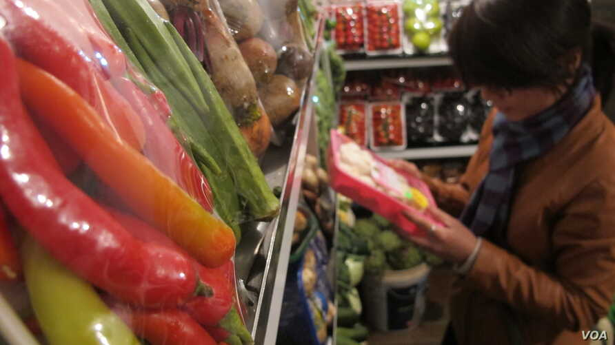 """A shopper reads packaging on vegetables on sale at Veggies, a grocery shop in central Hanoi listed on a website providing consumers with information on where to buy """"safe"""" vegetables, March 28, 2014. (Marianne Brown/VOA)"""