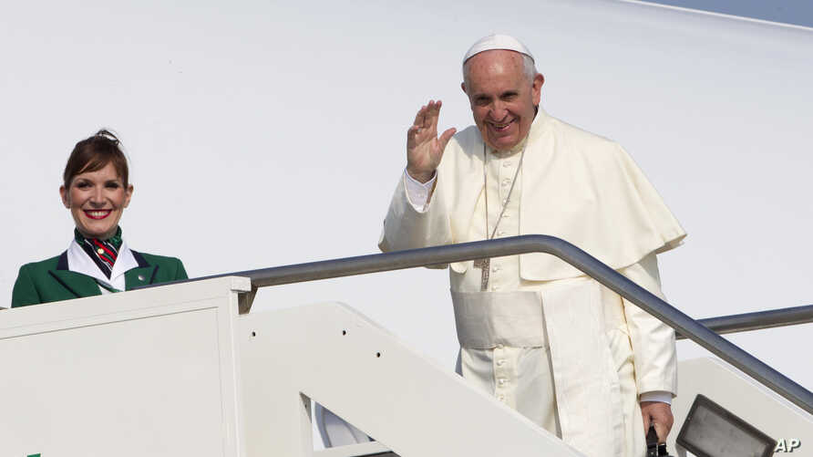 Pope Francis waves to reporters at Rome's Fiumicino international airport, July 5, 2015, as he boards his flight to Quito, Ecuador, where he will start a week-long trip to South America, including Bolivia and Paraguay.