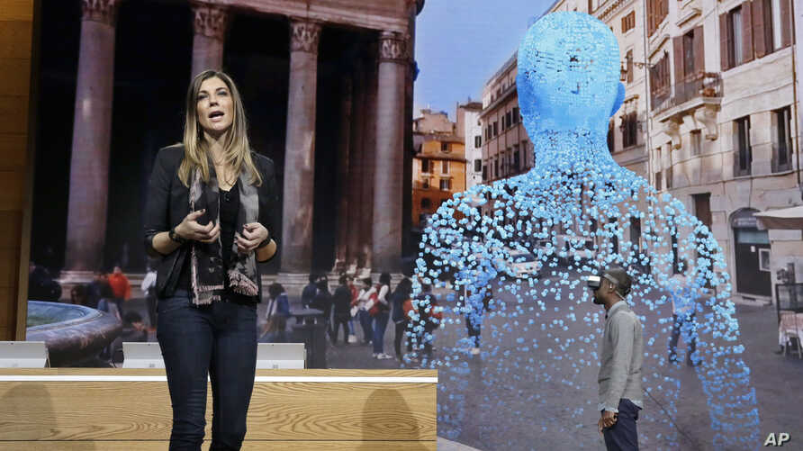 Megan Saunders, Microsoft's general manager, describes the capabilities of Paint 3D as Taj Reid experiences virtual reality at a Microsoft media event in New York, Oct. 26, 2016.