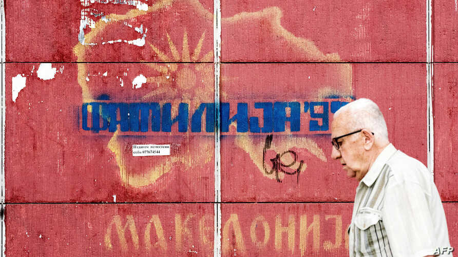 A man passes in front of graffiti with an old map of Macedonia referring to the long-running name row with neighboring Greece, in Skopje, June 13, 2018.
