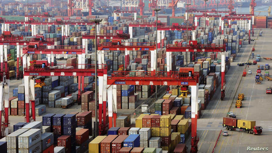 FILE - Trucks drive past piles of shipping containers at the Qingdao port in Qingdao, Shandong province, June 8, 2014.