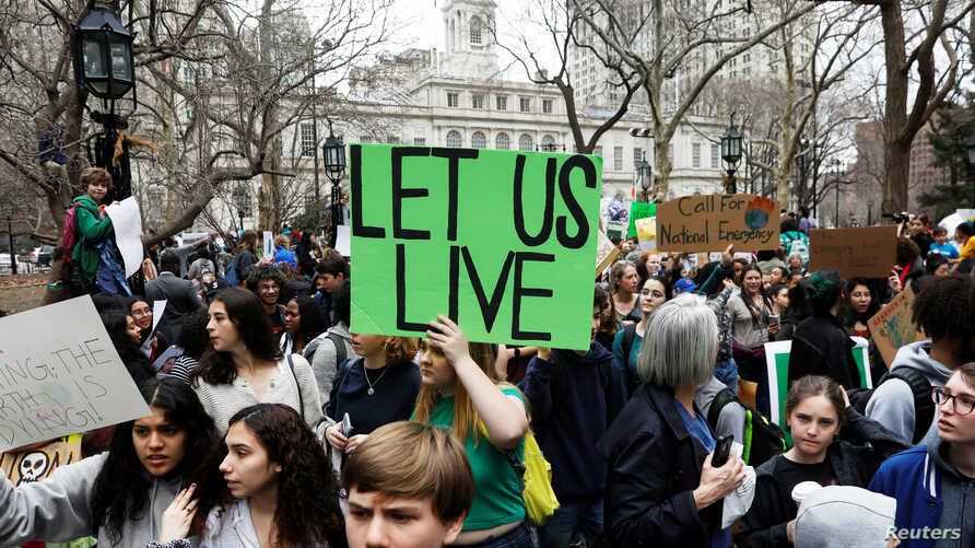 Students hold banners and placards during a demonstration against climate change in New York, March 15, 2019.