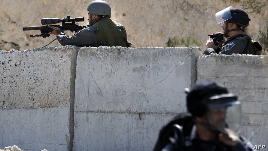 An Israeli security forces sniper aims his weapon toward Palestinian protesters during clashes in the east Jerusalem Arab neighborhood of Issawiya, Oct. 4, 2015.