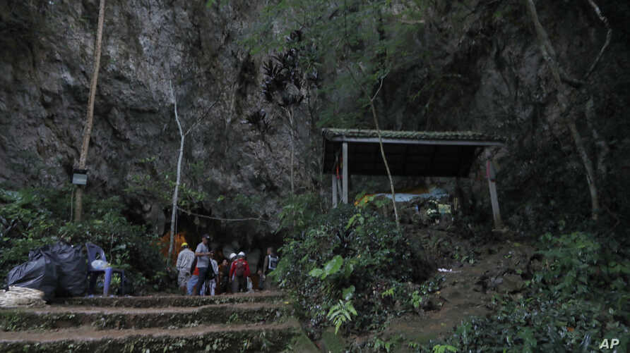 Rescue teams gather at the entrance of a deep cave where a group of boys went missing in Chiang Rai, northern Thailand, Monday, June 25, 2018.