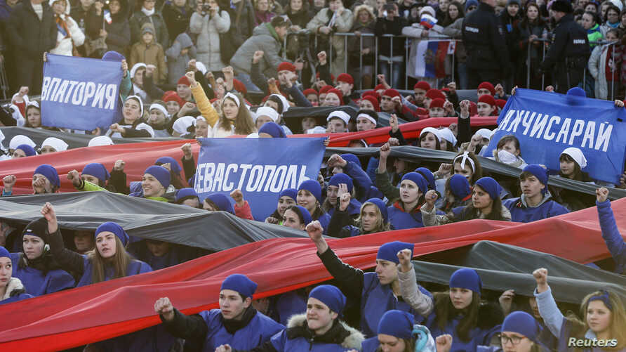 """Performers hold banners with names of Crimean cities during celebrations marking the first anniversary of Russia's annexation of Ukraine's Black Sea peninsula of Crimea, in central Simferopol, March 16, 2015. The placards read (L-R), """"Yevpatoriya,"""" """""""