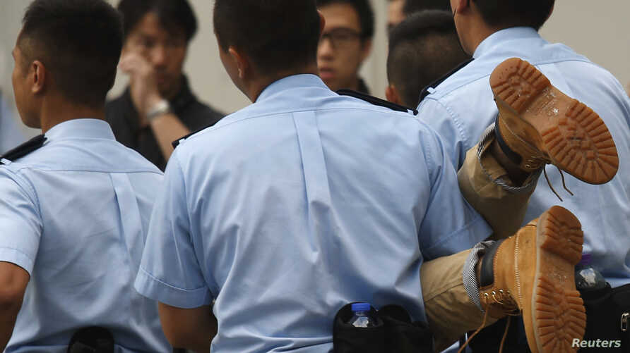 A protester is carried away by police officers from a street after staying overnight at Hong Kong's financial Central district July 2, 2014. Pro-democracy protesters gathered for a mass march in Hong Kong on Tuesday, with one burning a photograph of