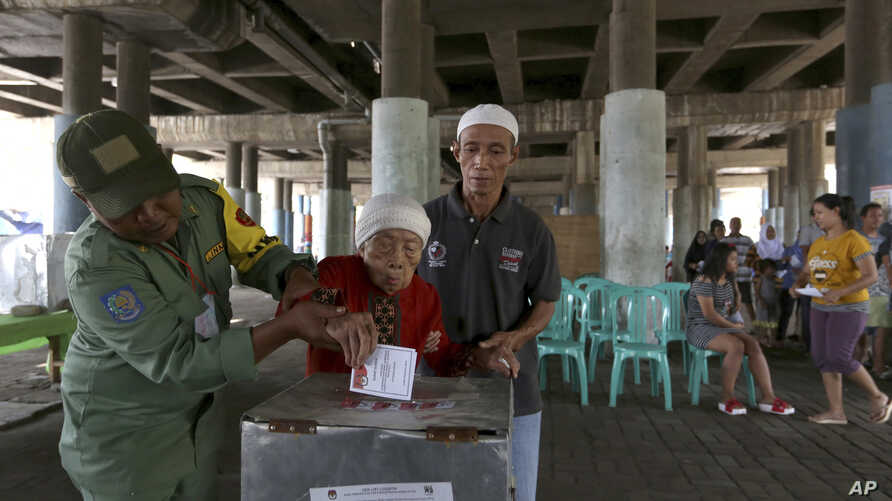 Electoral workers help an elderly woman cast her ballot at a makeshift polling station under a bridge during the runoff election in Jakarta, Indonesia, April 19, 2017.