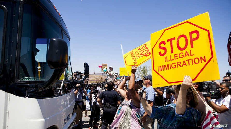 FILE - Demonstrators rally against the arrival of undocumented migrants who were scheduled to be processed at the Murrieta Border Patrol Station in Murrieta, California, July 1, 2014.