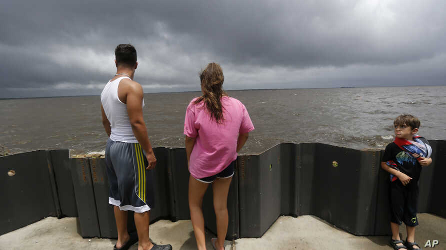 Jonas Cheramie (left) and his sister Lainey Cheramie, watch storm clouds from Tropical Storm Cindy, as they babysit A.J. Aaron, 5, in Lafitte, La., June 21, 2017.