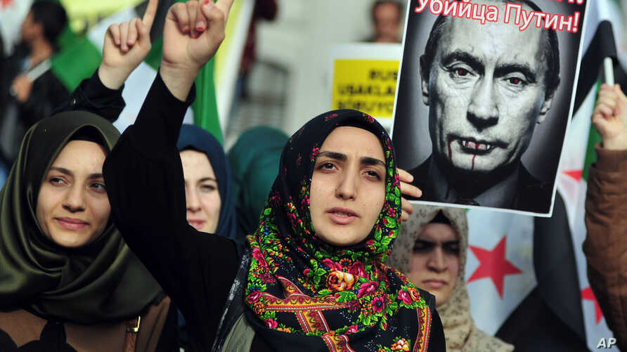 """Turkish protesters shout anti-Russia slogans as they hold a poster of Russian President Vladimir Putin that reads in Turkish and Russian """" Assassin Putin! """" during a protest in Istanbul, Turkey, Nov. 27, 2015."""