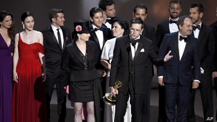 """Amy Sherman-Palladino, front and center left, Daniel Palladino and the cast and crew of """"The Marvelous Mrs. Maisel"""" accept the award for outstanding comedy series at the 70th Primetime Emmy Awards, Sept. 17, 2018, at the Microsoft Theater in Los Ange"""