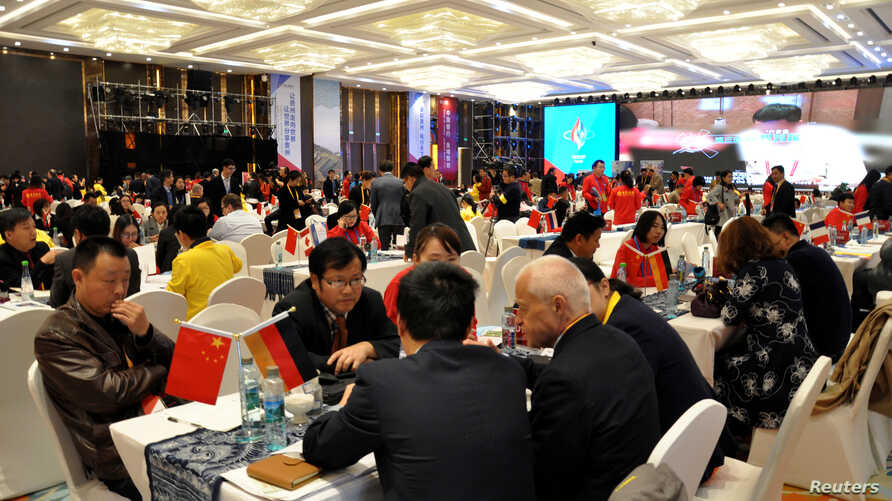 FILE - Local businessmen and foreign investors negotiate at a cross-border investment and trade fair in Guiyang, Guizhou Province, China, Nov. 10, 2016.