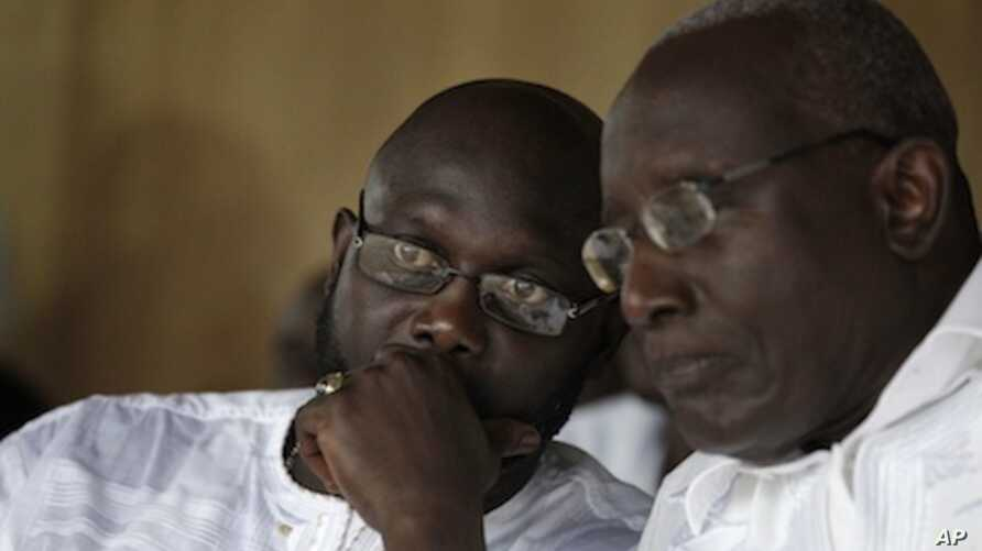 Liberian opposition presidential candidate Winston Tubman, right, talks with running mate George Weah at a rally urging their party's supporters to boycott next week's presidential polls, in Monrovia, Liberia Saturday, Nov. 5, 2011.
