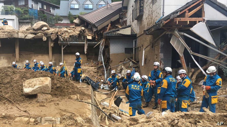 Emergency teams rest outside building with structural damage caused by heavy rains, July 9, 2018, in Hiroshima, Japan.