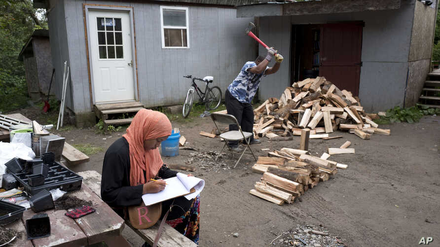 FILE - A girl studies for school while a man chops wood in the Muslim enclave of Islamberg in Tompkins, New York.