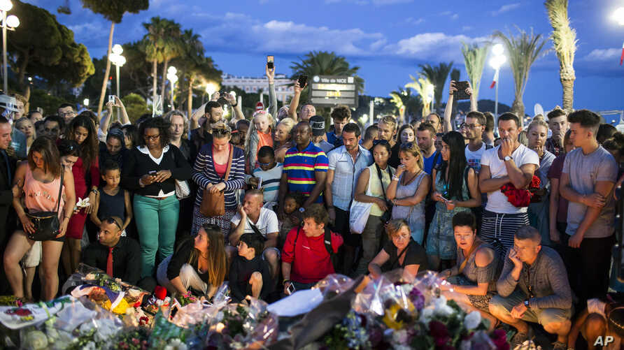 People gather at a makeshift memorial to honor the victims of an attack, near the area where a truck mowed through revelers in Nice, France, July 15, 2016.