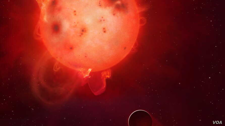 The planet Kepler-438b is shown here in front of its violent parent star. It is regularly irradiated by huge flares of radiation, which could render the planet uninhabitable. Here the planet's atmosphere is shown being stripped away.