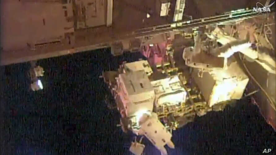 In this frame grab from NASA Television, astronauts Scott Kelly, upper right, and Kjell Lindgren, bottom, perform maintenance outside the International Space Station, Oct. 28, 2015.