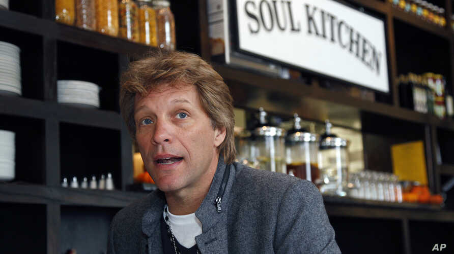 FILE- In this Oct. 19, 2011, file photo, rock star Jon Bon Jovi sits in his JBJ Soul Kitchen community restaurant in Red Bank, N.J. The restaurant is providing free meals to local government workers and their families during the federal government sh