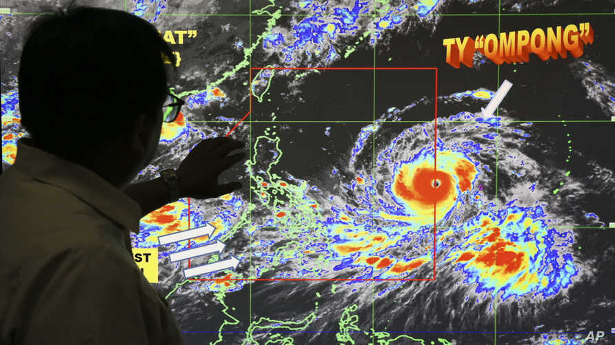 """Forecaster Meno Mendoza shows the path of Super Typhoon Mangkhut, locally named """"Typhoon Ompong,"""" as it approaches the Philippines at the Philippine Atmospheric, Geophysical and Astronomical Services Administration in Manila, Sept. 12, 2018."""