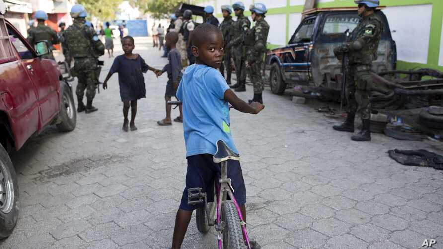 In this Feb. 22, 2017 photo, children play in the street while U.N. peacekeepers from Brazil patrol in the Cite Soleil slum, in Port-au-Prince, Haiti.
