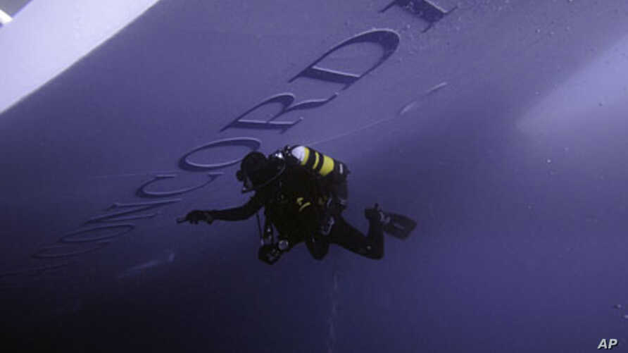 A Carabinieri scuba diver inspects the Costa Concordia cruise ship which ran aground off the west coast of Italy at Giglio island January 19, 2012.