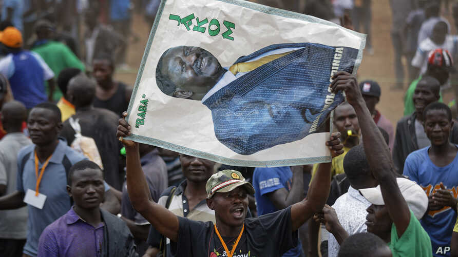 "A supporter of Kenyan opposition leader Raila Odinga holds a banner of him with the Swahili words ""Father"" and ""Chairman"" at a rally in the Shauri Moyo area of Nairobi, Kenya, Oct. 18, 2017"