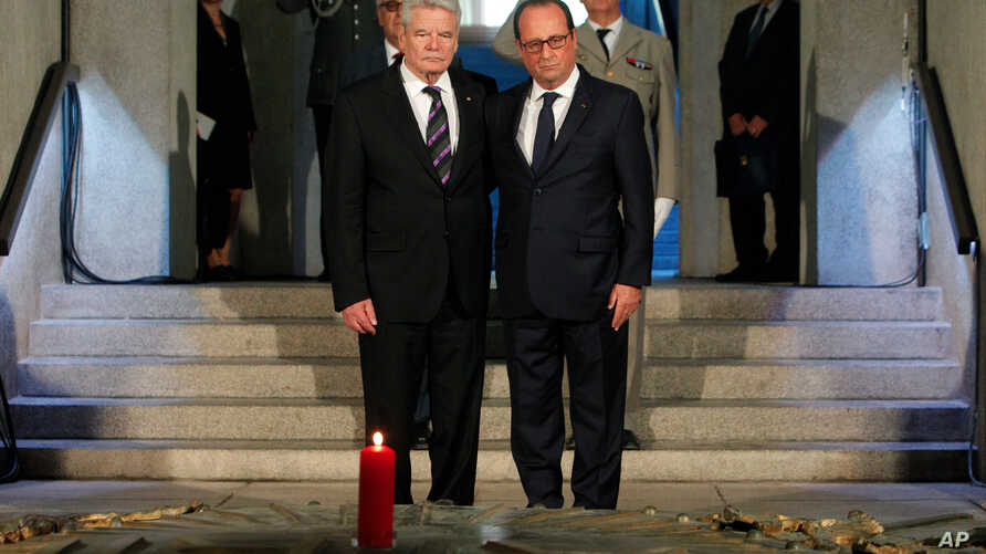 France's President Francois Hollande, right, stands with German President Joachim Gauck, left, as they pay respect in the crypt of the the National Monument of Hartmannswillerkop, in Wattwiller, eastern France, Aug. 3, 2014, to mark the 100th anniver...
