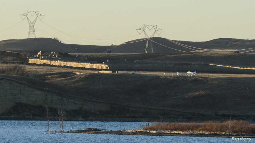FILE - Dakota Access Pipeline equipment is seen near Lake Oahe, near the Standing Rock Indian Reservation, in this picture taken from across the Missouri River in Linton, North Dakota, Nov. 9, 2016.