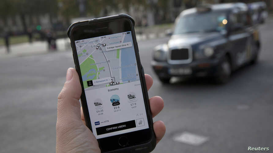 A photo illustration shows the Uber app on a mobile telephone in front of a London Taxi, in London, Britain, Nov. 10, 2017.