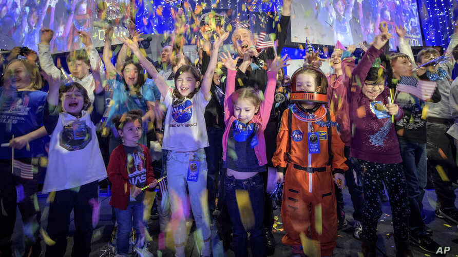 In this photo provided by NASA, a NASA scientist celebrates with school children at the exact moment that the New Horizons spacecraft made the closest approach of Kuiper Belt object Ultima Thule, Jan. 1, 2019, at Johns Hopkins University Applied Phys...