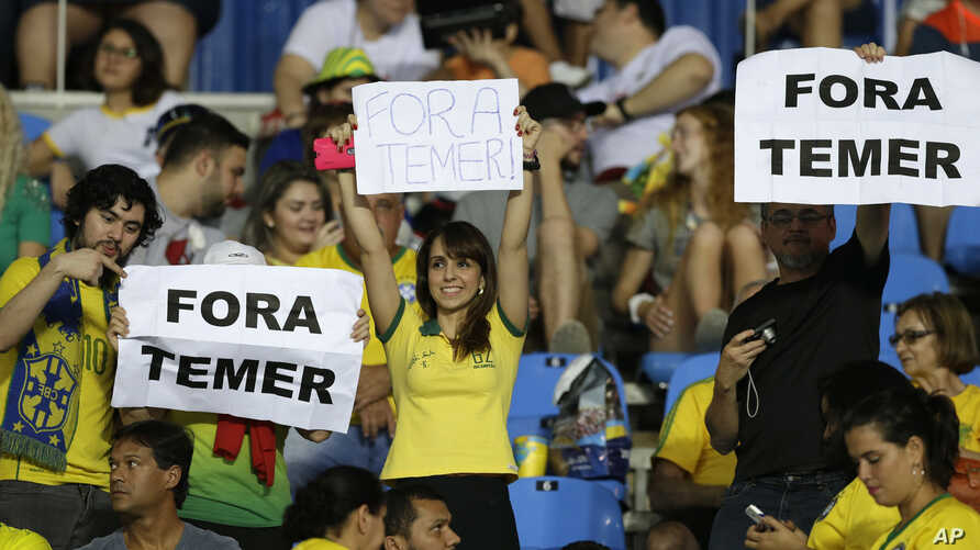 """fans hold signs that read in Portuguese; """"Temer Out"""" prior to a group E match of the women's Olympic football tournament between Brazil and Sweden at the Rio Olympic Stadium in Rio de Janeiro, Brazil, Aug. 6, 2016."""