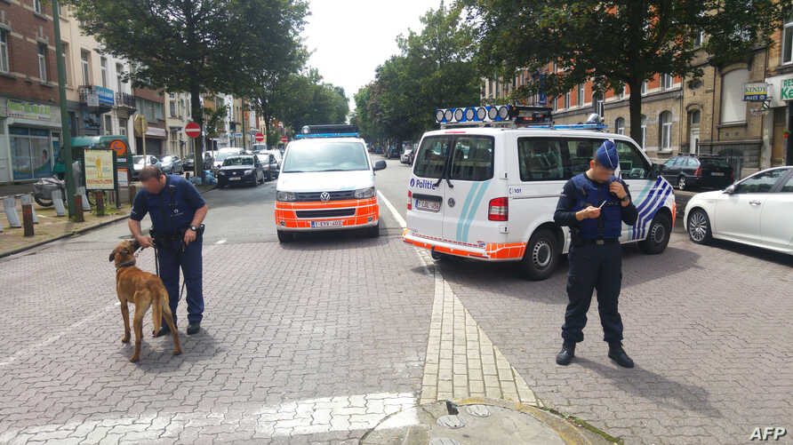 A picture taken with a smartphone on June 17, 2016 shows Belgian police officers standing guard in the Kazernelaan - Avenue des Casernes, in the district of Etterbeek, in Brussels, where terrorists Osama Krayem and Khalid El Bakraoui lived before the