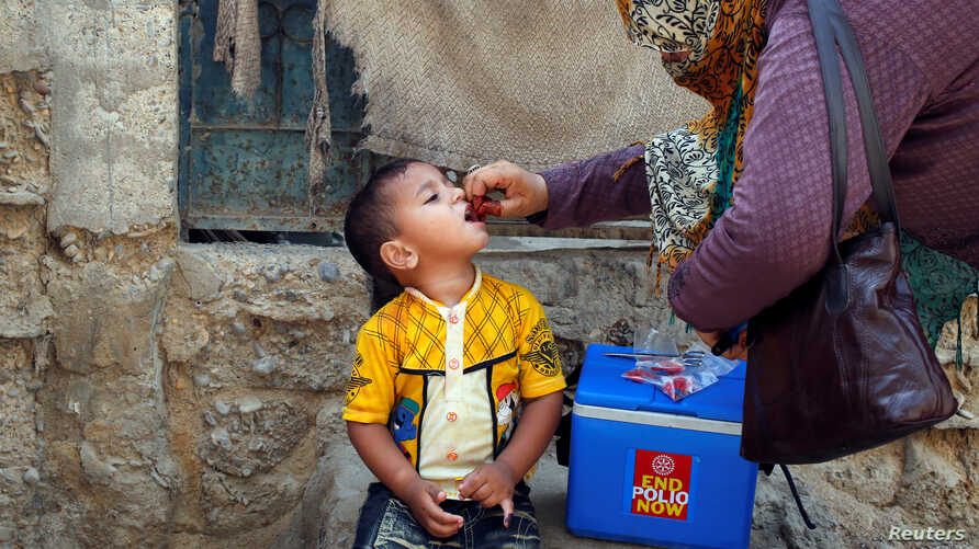 A boy receives polio vaccine drops, during an anti-polio campaign, in a low-income neighbourhood in Karachi, Pakistan April 9, 2018.