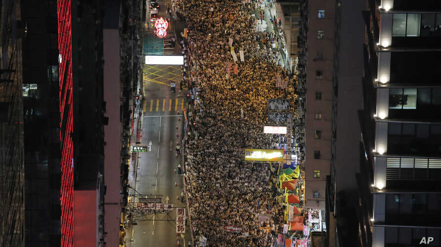 People march during an annual protest in downtown Hong Kong Tuesday, July 1, 2014.