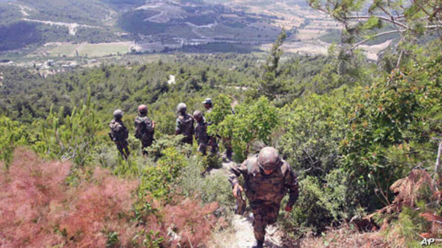 A picture taken on a tour organized by the Syrian Red Crescent shows Syrian soldiers deploying along the Syrian-Turkish border near the village of Khirbet al-Joz in the northern province of Idlib, June 29, 2011