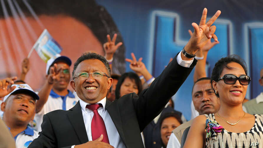 FILE - Hery Rajaonarimampianina (L) acknowledges the crowd with his wife Lalao (R) at anelection campaign rally in Antananarivo, Madagascar, in October 2013.