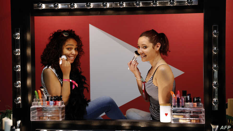 """FILE - Girls look in a mirror as they put makeup on during a beauty and fashion fair inspired by the US """"Beautycon"""" event, a  gathering of fashion bloggers and YouTube personalities, May 28, 2016, in Paris. Researchers found that in most of the world"""