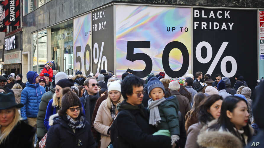 Crowds walk past a large store sign displaying a Black Friday discount in midtown Manhattan, Nov. 23, 2018, in New York.
